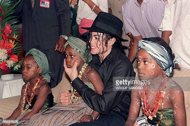US pop star and entertainer Michael Jackson sits with orphaned and abandoned Ivory Coast children he invited to the Intercontinental Hotel in Abidjan...