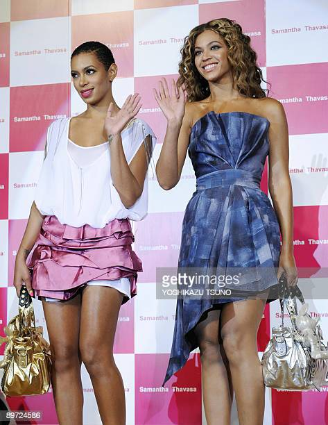 US pop star Beyonce Knowles and her younger sister Solange wave as they display bags and accessories featuring Disney characters by Japanese fashion...