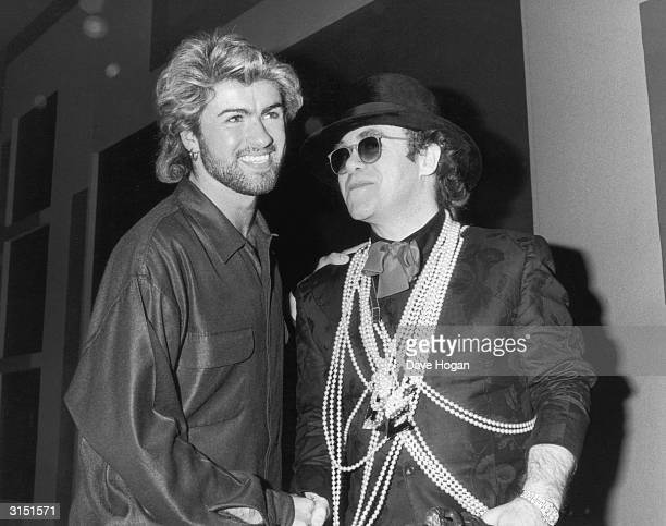 Pop star Elton John congratulates George Michael on winning the Ivor Novello Songwriter of the Year Award at London's Grosvenor House Hotel, 13th...