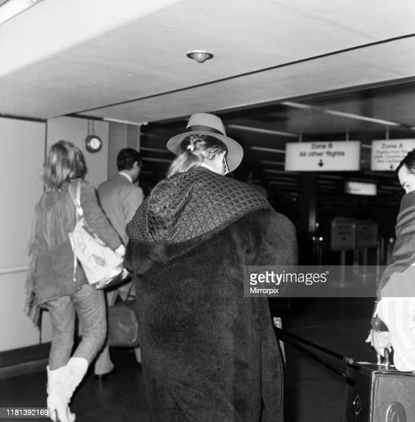 Pop star Elton John pictured showing off his pony tail as he arrives at London's Heathrow Airport from Los Angeles 17th October 1986