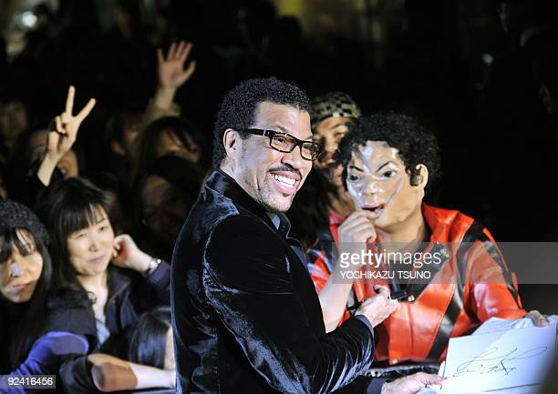 US pop star Lionel Richie gives his autograph to a Japanese fan wearing a Michael Jackson mask on the red carpet of the Japan premiere of Michael...