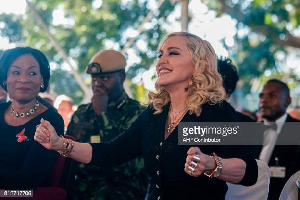 US pop star Madonna dances as Malawi's first lady Gertrude Mutharika looks on during the opening ceremony of the Mercy James Children's Hospital at...
