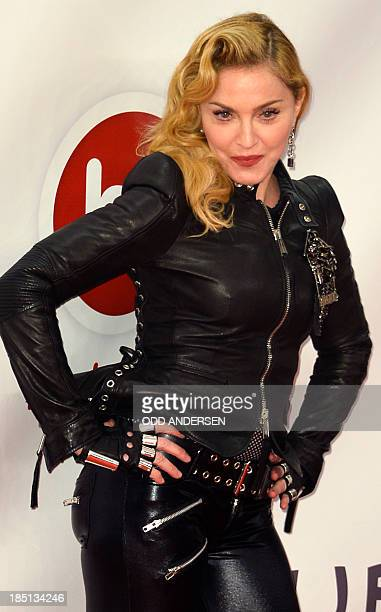 US pop star Madonna poses for photographers on the red carpet on the opening event of the Fitness Center Hard Candy on October 17 2013 in Berlin AFP...