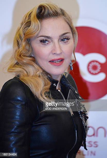 US pop star Madonna poses for photographers on the red carpet on the opening event of the Fitness Center Hard Candy on October 17 2013 in BerlinThe...
