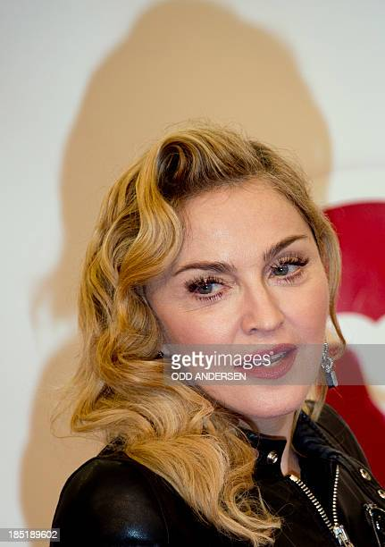 US pop star Madonna poses on the red carpet arriving for the opening of the 'Hard Candy' fitness Center in Berlin on October 17 2013 AFP PHOTO / ODD...