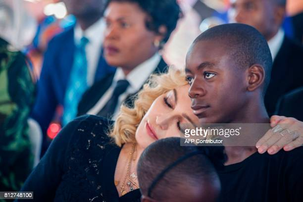 US pop star Madonna rests her head on the shoulder of her adopted son David Banda during the opening ceremony of the Mercy James Children's Hospital...