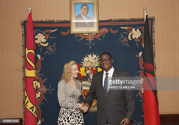 US pop Star Madonna shakes hands with Malawi's president Professor Peter Mutharika prior to their meeting at Kamuzu Palace in the Capital Lilongwe on...