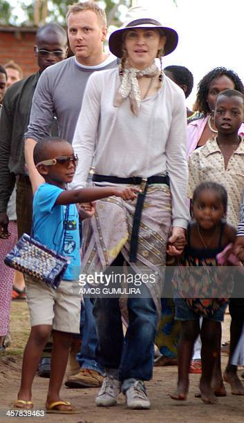 US Pop Star Madonna walks with her adopted son David Banda and adopted daughter Mercy Chifundo James during a visit to Mphandula Child Care Centre at...