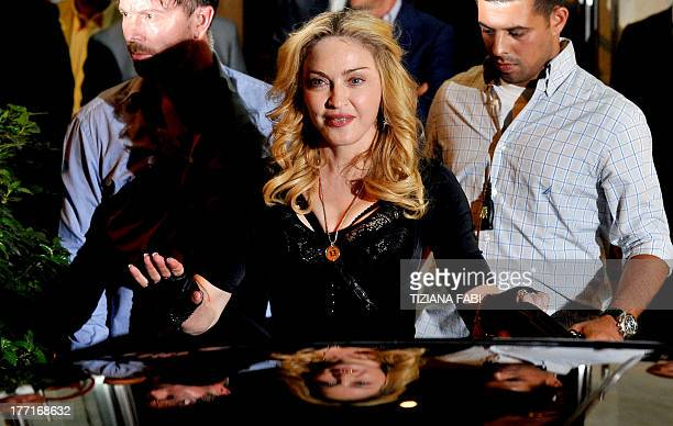 US pop star Madonna waves after visiting a Hard Candy Fitness center in central Rome on August 21 2013 The fitness clubs are part of a global chain...