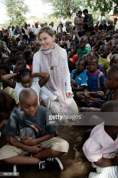 US Pop Star Madonna with her Malawian adopted children David and Mercy sit among Malawian children during a visit to Mkoko Primary School on April 2...