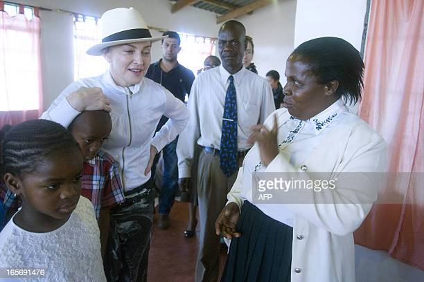 US Pop Star Madonna with her Malawian adopted children David and Mercy is briefed by Executive Director of Mphandula Childrencare Centre on what...