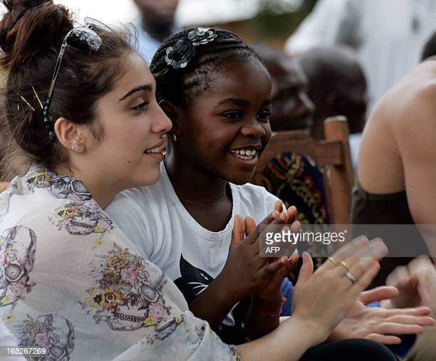 US Pop Star Madonna's biological daughter Loudes and adopted daughter Mercy James clap hands during a visit to Mkoko Primary School on April 2 2013...