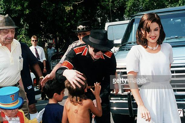 US pop star Michael Jackson and his wife Lisa Marie Presley salute children in Budapest 6 August 1994 Jackson is starting a three day visit to film...