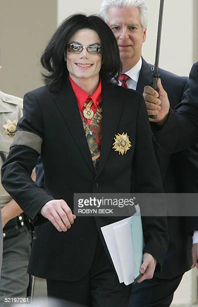 US pop star Michael Jackson carries papers as he strides out of court in Santa Maria CA 14 February 2005 after a day in the critical jury selection...