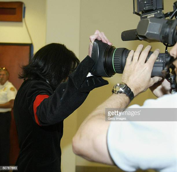 Pop star Michael Jackson covers the lens of a camera to avoid being filmed as he enters the Santa Maria Courthouse April 30 2004 in Santa Maria...