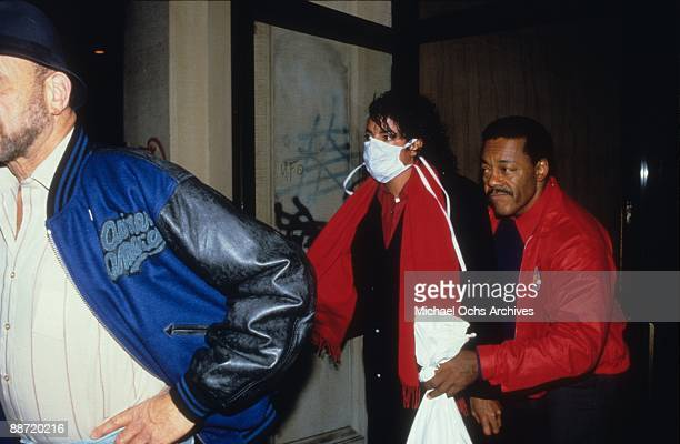 Pop Star Michael Jackson gets ushered in to a building wearing a surgical mask in circa 1990