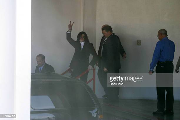 Pop star Michael Jackson gives the peace sign as he leaves the Santa Barbara County Jail after surrendering on multiple counts of molesting a child...