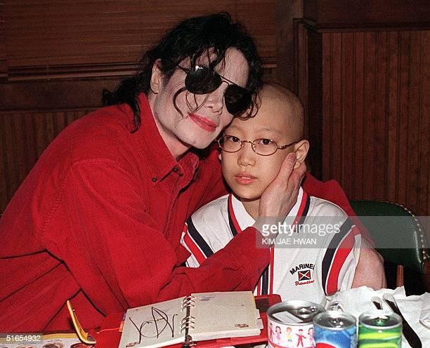 US pop star Michael Jackson hugs 11 yearold blood cancer child Lim JaeHeon in his arms 23 June 1999 in the Bennigun's restaurant in Seoul Jackson is...