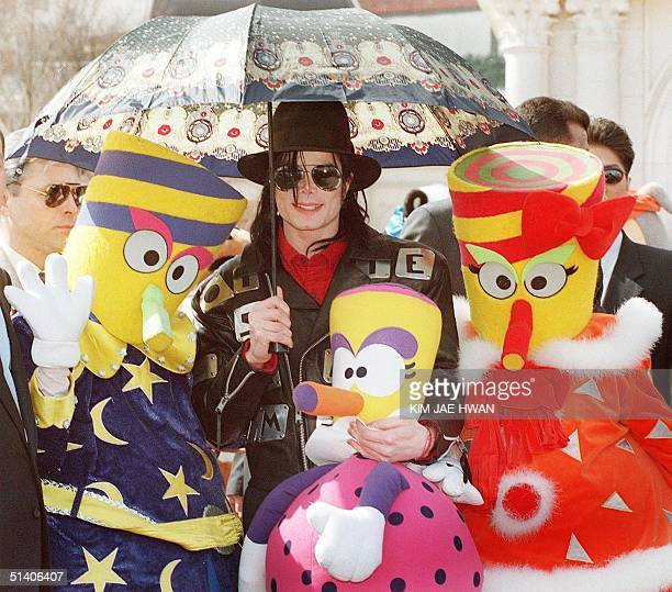 Pop star Michael Jackson poses 23 February with three 'Everland characters' during his tour to the country's largest amusement park Everland in...