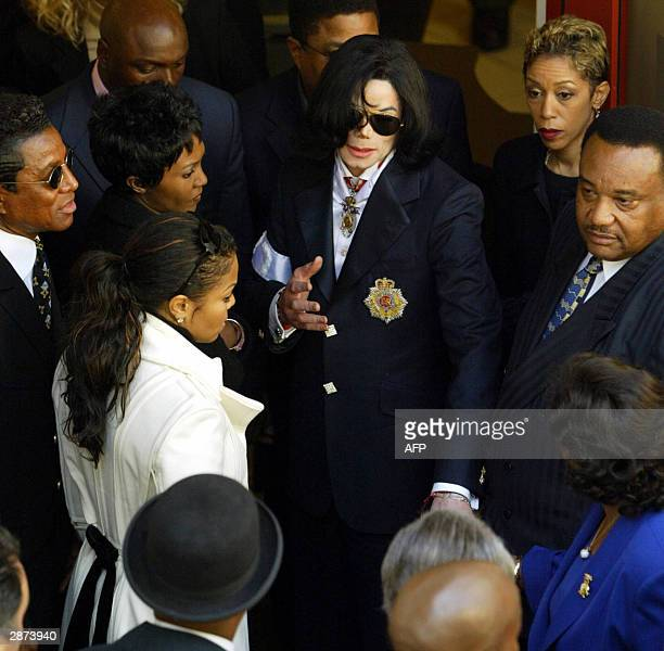 Pop star Michael Jackson reaches out to touch the hand of his mother Kathleen as he is encircled by his immediate family including his sister Janet...
