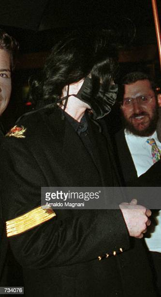 Pop star Michael Jackson surprised by paparazzi pulls up his mask November 20 2000 as he leaves the Denise Rich building on 5th Ave and 60th St...