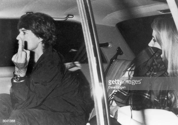 Pop star Mick Jagger gives the photographer the finger from inside a car, circa 1980.