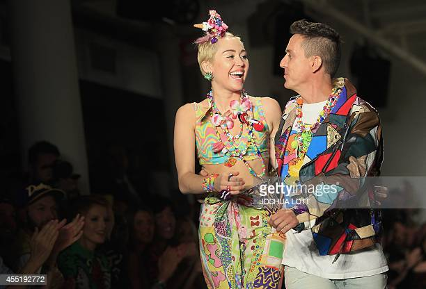 US pop star Miley Cyrus and designer Jeremy Scott walk the runway during his Spring/Summer 2015 collection at York Fashion Week September 10 2014 in...