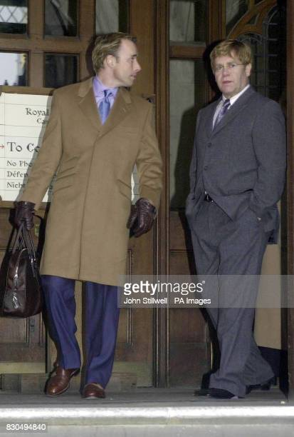 Pop star Sir Elton John and his partner David Furnish leave the High Court in London for lunch after giving evidence in his multimillion pound...