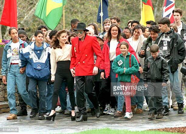 Pop superstar Michael Jackson holding hands with his wife Lisa Marie Presley walks with children at his Neverland Ranch in Los Olivos California as...