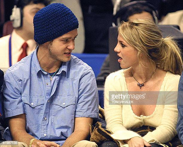 Pop superstars Britney Spears and boyfriend Justin Timberlake talk as they sit courtside at the NBA AllStar Game 10 February 2002 in Philadelphia