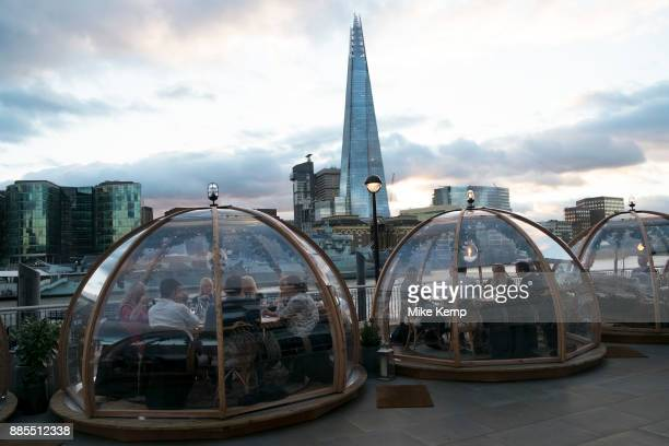 Pop up igloos being used for diners outside a hotel restaurant opposite The Shard in London England United Kingdom