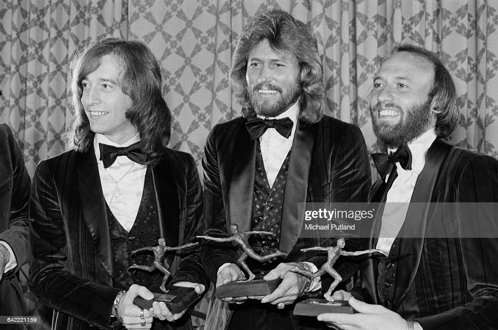 Pop vocal trio The Bee Gees after receiving the annual Superstars award given by the Police Athletic League for charity work, at the Sheraton Center, New York City, 8th January 1979. The group are being honoured for the benefits thay played in aid of the PAL. Left to right: Robin Gibb (1949 - 2012), Barry Gibb and Maurice Gibb (1949 - 2003).