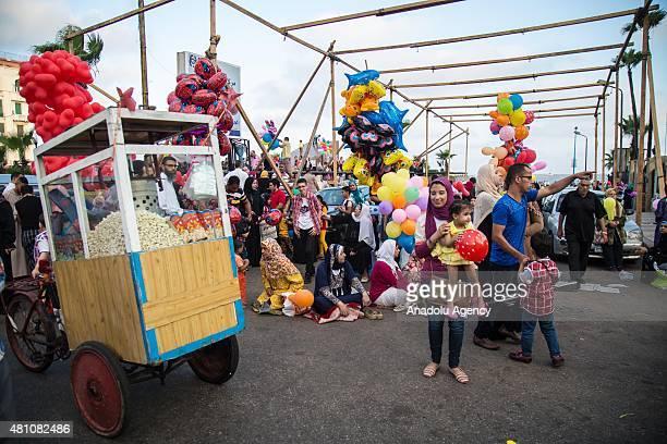 Popcorn and balloon peddlers seen as muslims perform Eid elFitr prayer at El Qaed Ibrahim Mosque in Alexandria Egypt on July 17 2015 Eid alFitr is a...