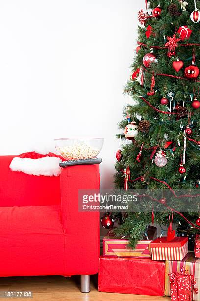 Popcorn bowl and remote on sofa with christmas tree