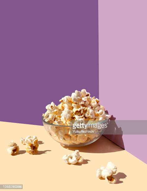 popcorn bowl on the purple-beige background- frontal view - ポップコーン ストックフォトと画像