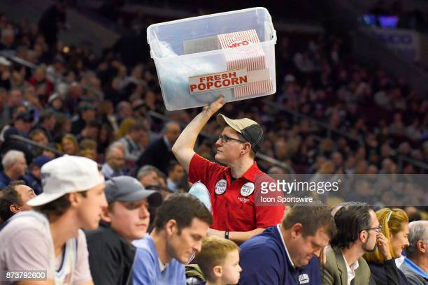 A popcorn / cotton candy seller holds his goods high as he makes his way through the crowd during the college basketball game between the Columbia...