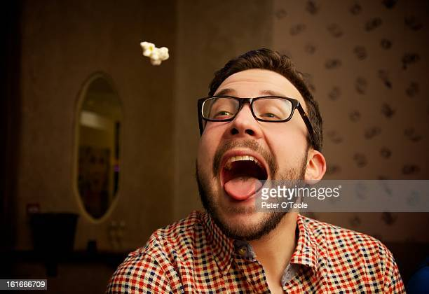 popcorn thrown into mouth of a young bearded man - mouth open stock pictures, royalty-free photos & images