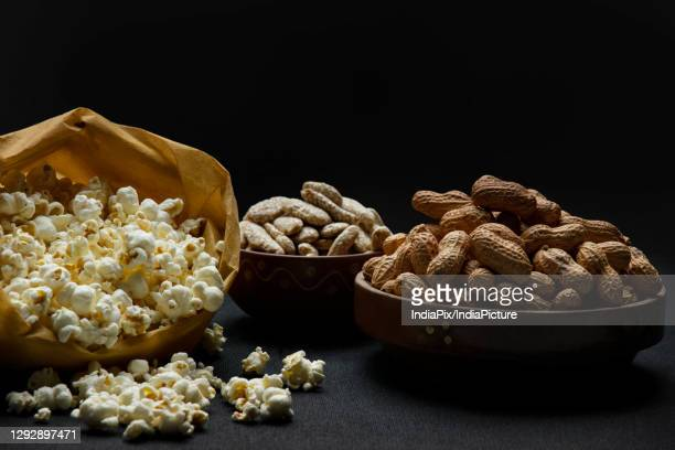 popcorns in a brown bag kept alongside bowls of rewari and groundnuts. - lohri festival stock pictures, royalty-free photos & images