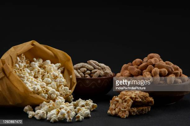 popcorns in a brown bag kept alongside chikki and bowls of rewari and groundnuts. - lohri festival stock pictures, royalty-free photos & images