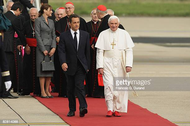 Pope Benedict XVI arrives at Orly airport welcomed by French President Nicolas Sarkozy and his wife Carla BruniSarkozy on September 12 2008 in Paris...
