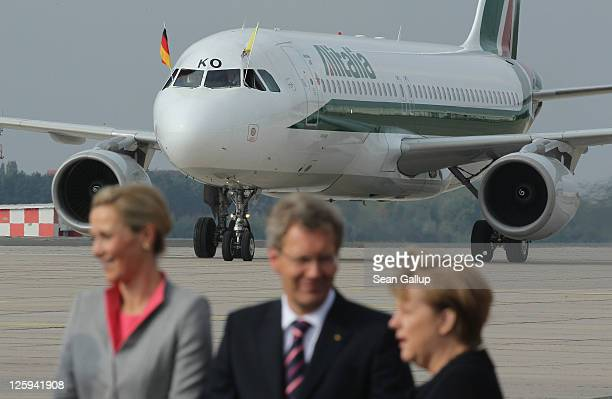 Pope Benedict XVI arrives in his Papal plane as German President Christian Wulff , German Chancellor Angela Merkel and First Lady Bettina Wulff wait...
