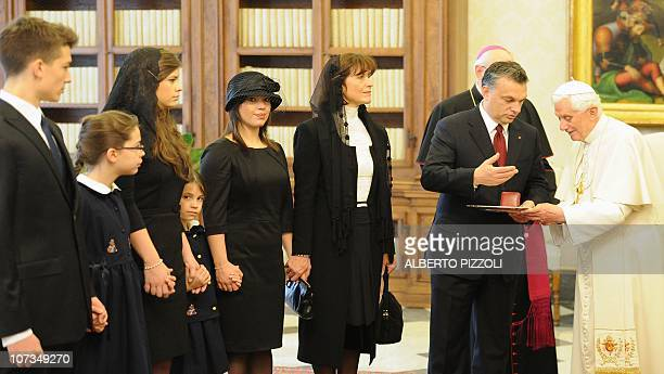Pope Benedict XVI exchanges gifts with Hungary's Prime Minister Viktor Orban as Orban's wife Aniko Levai and their five children watch during a...