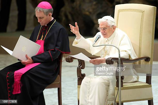 Pope Benedict XVI flanked by his personal secretary Georg Gaenswein waves to the faithful gathered at the Paul VI Hall during his weekly audience on...