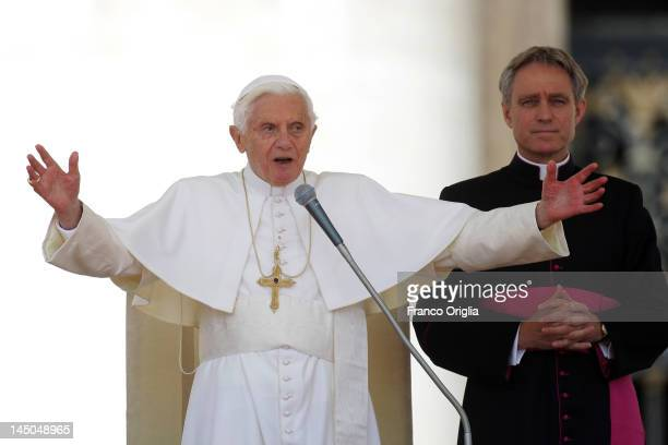 Pope Benedict XVI flanked by his personal secretary Georg Ganswein blesses faithful gathered in St Peter's Square during his weekly audience on May...