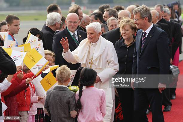 Pope Benedict XVI greets children upon his arrival at Tegel airport as German President Christian Wulff and German Chancellor Angela Merkel look on...