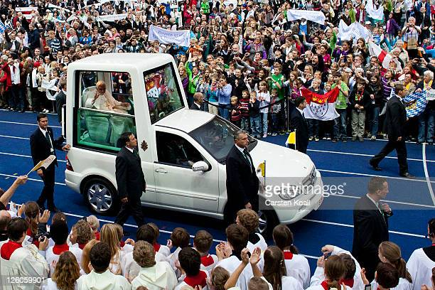 Pope Benedict XVI greets visitors while riding in the Popemobile upon his arrival at Olympiastadion stadium where he later gave a Catholic mass for...