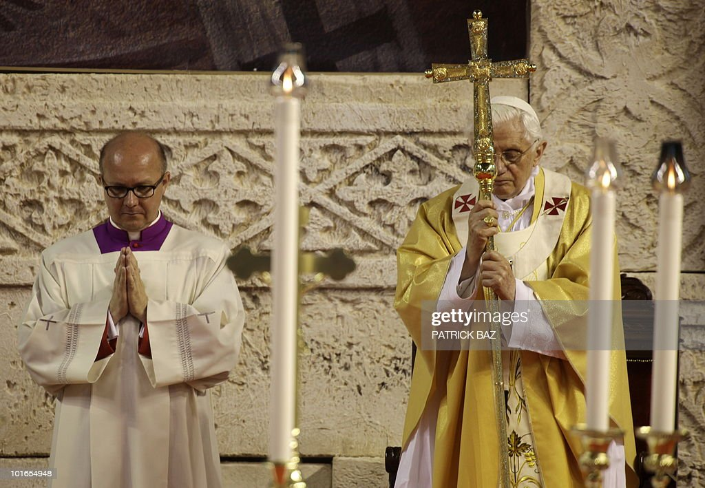 Pope Benedict XVI holds a cross during a holy mass at the Eleftheria Sports Centre in Nicosia on June 6, 2010 on the third and final day of the pontiff's visit to the mostly Greek Orthodox Mediterranean island.