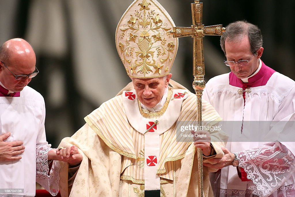 Pope Benedict XVI is helped as he attends the Christmas night mass at the St. Peter's Basilica on December 24, 2012 in Vatican City, Vatican.