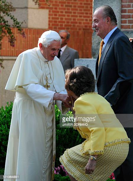 Pope Benedict XVI is kissed by Spain's Queen Sofia under the look of Spain's King Juan Carlos as he arrives for a visit at the Zarzuela Palace in...