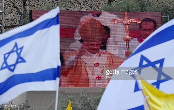 Pope Benedict XVI is seen on a screen as he waves to the faithful at the conclusion of a mass at the Garden of Gethsemane at the foot of the Mount of...